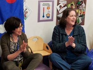 Barbara Andrews (right) joins an early childhood teacher in a child and parent activity at the ECS classroom.