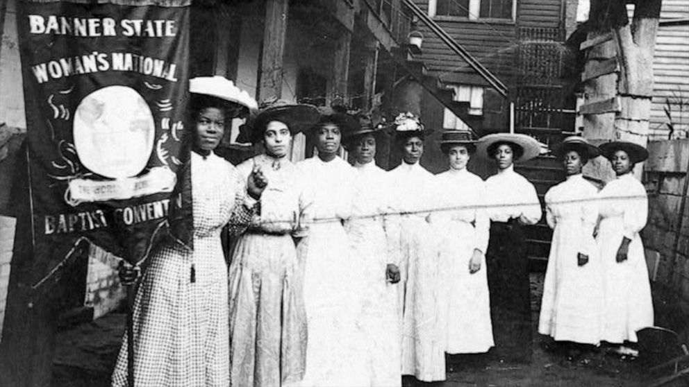 "Nine African-American women pose for a photo with Nannie Burroughs, holding a banner that reads, ""Banner State Woman's National Baptist Convention,"" circa 1905."